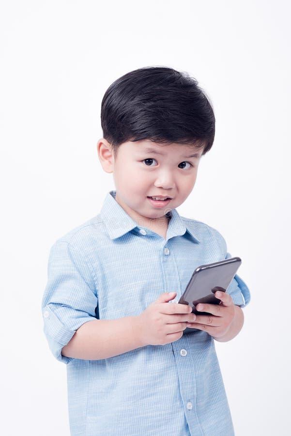 Garçon jouant le téléphone portable sur le fond blanc photo stock