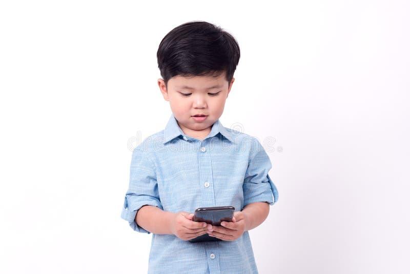 Garçon jouant le téléphone portable sur le fond blanc images stock