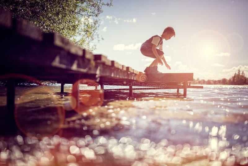 Garçon jouant sur un pilier par le lac des vacances d'été image libre de droits