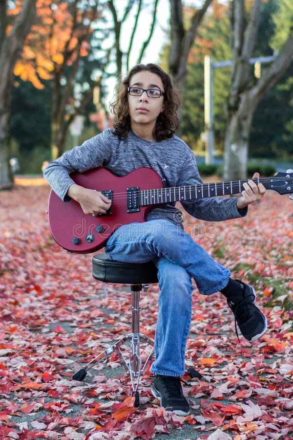 Garçon jouant une guitare rouge images stock