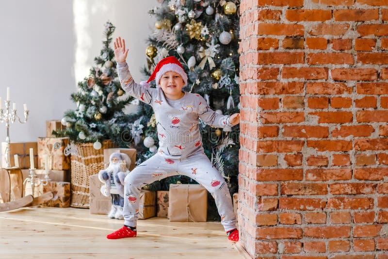 Garçon joyeux de huit ans en pyjama et chapeau de Père Noël près d'un magnifique arbre de Noël photos stock