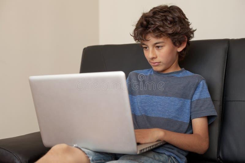 Garçon latin s'asseyant sur le sofa avec l'ordinateur portable photo stock