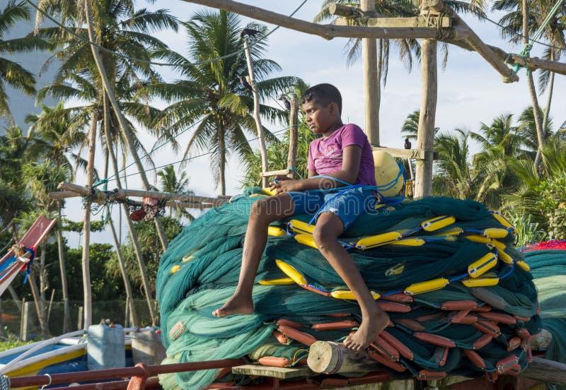 Garçon local s'asseyant sur les filets de pêche dans le bateau photos stock