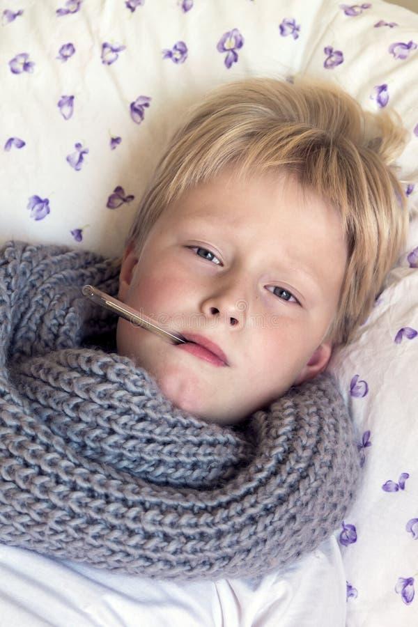Garçon malade avec le thermomètre photographie stock