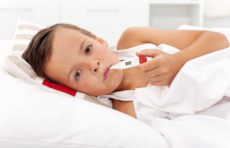 Garçon malade avec le thermomètre prenant la température photographie stock