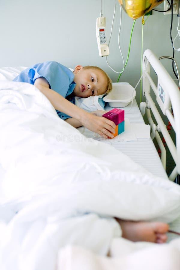 Garçon malade dans le bâti d'hôpital avec son jouet photographie stock libre de droits