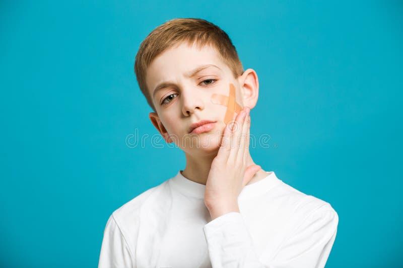 Garçon malheureux dans des vêtements blancs tenant l'emplâtre adhésif sur son che image stock