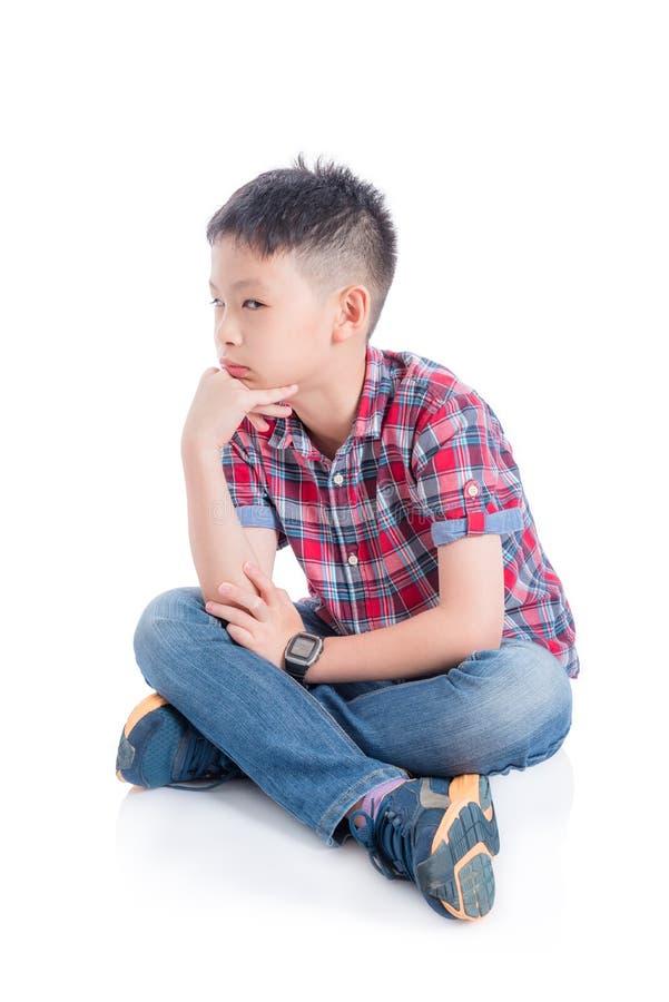 Garçon malheureux s'asseyant sur le plancher au-dessus du blanc photos libres de droits
