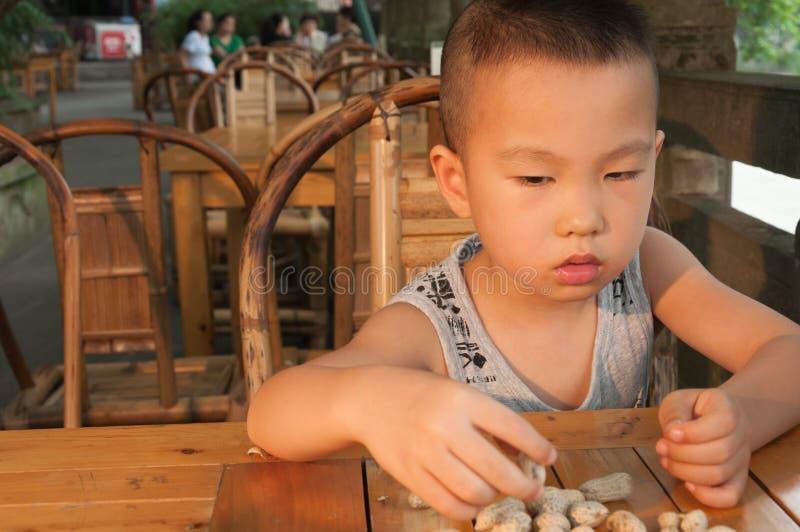 Garçon mangeant des arachides photos stock