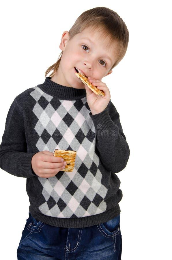 Garçon mangeant des biscuits photos stock