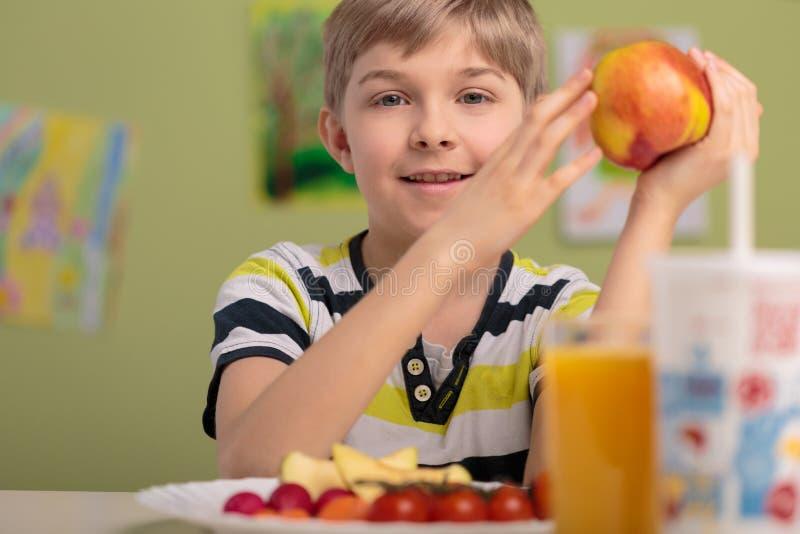 Garçon mangeant des fruits pour le déjeuner photos stock