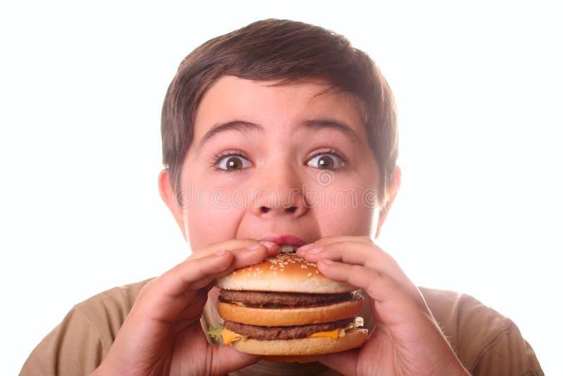 garçon mangeant des jeunes d'hamburger images stock