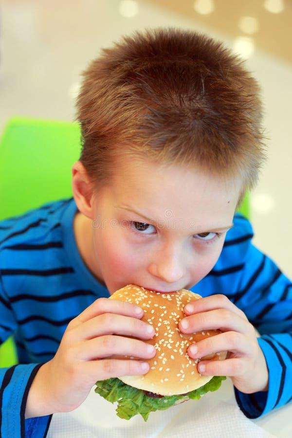 Garçon mangeant l'hamburger image stock