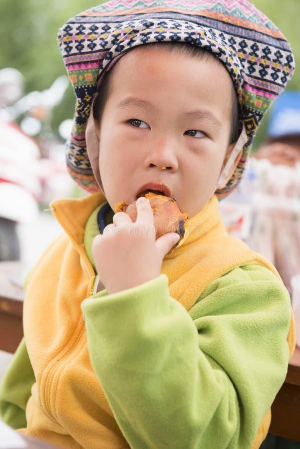 Garçon mangeant la patate douce cuite au four photo stock