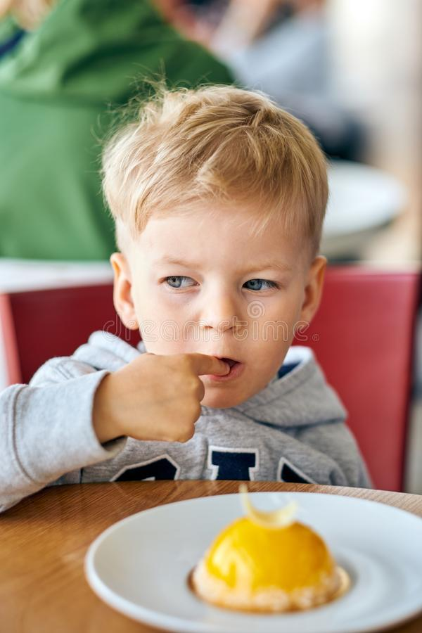 Garçon mangeant le dessert en café image stock