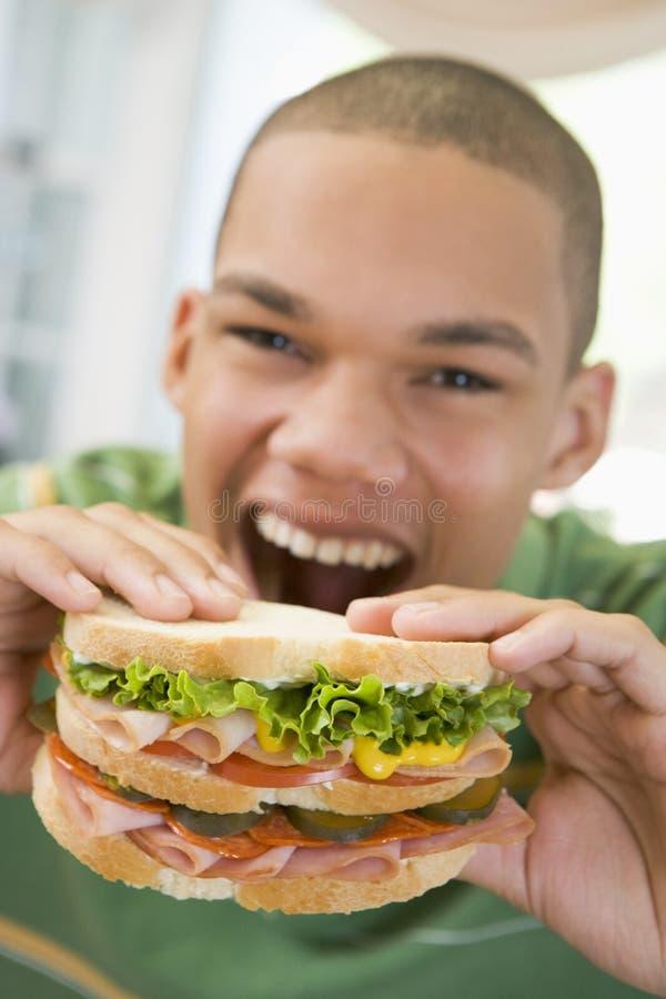 garçon mangeant le sandwich d'adolescent image stock