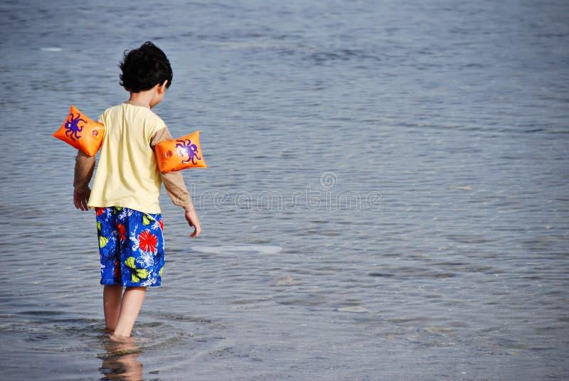 Garçon marchant en mer image stock