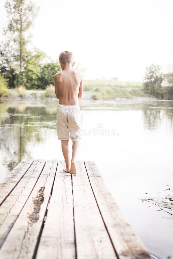 Garçon marchant sur le dock image stock