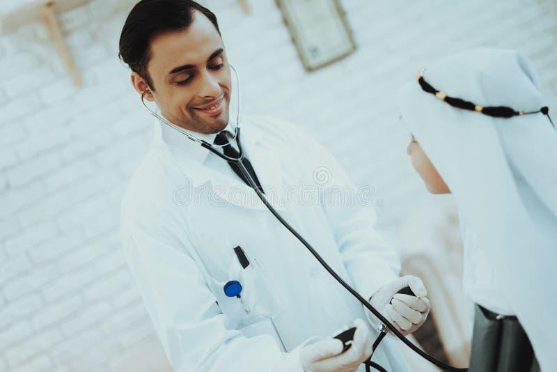 Garçon masculin arabe de docteur Checking Blood Pressure photo libre de droits