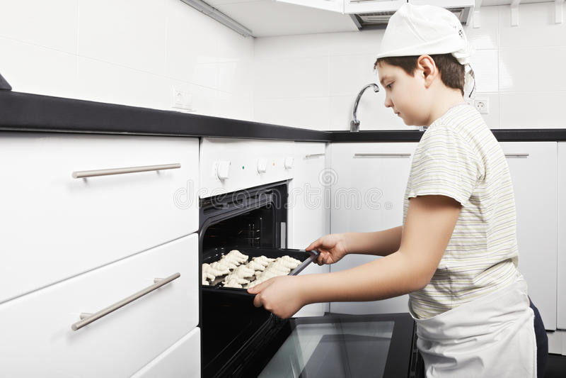 Garçon mettant des croissants dans le four photographie stock