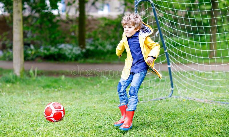 Garçon mignon actif de petit enfant jouant le football et le football et ayant l'amusement photographie stock