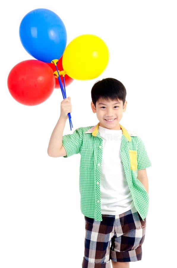 Garçon mignon asiatique heureux avec les ballons colorés photo libre de droits