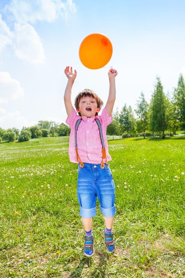 Garçon mignon avec le ballon orange dans le domaine vert photo libre de droits