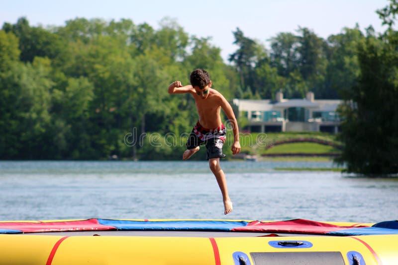 Garçon mignon beau sautant à un trempoline de l'eau flottant dans un lac au Michigan pendant l'été image libre de droits