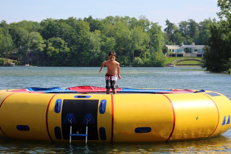 Garçon mignon beau sautant à un trempoline de l'eau flottant dans un lac au Michigan pendant l'été photographie stock