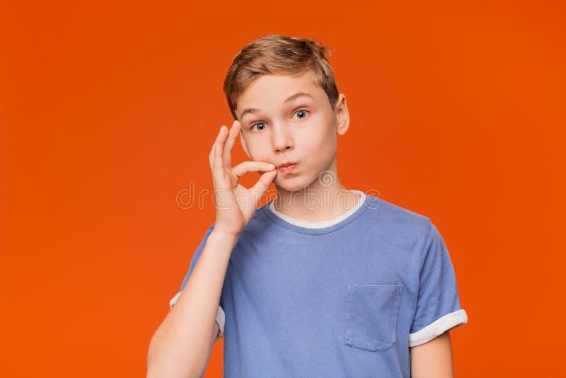 Garçon mignon d'adolescent fermant à clef la bouche comme le zip-lock photographie stock libre de droits