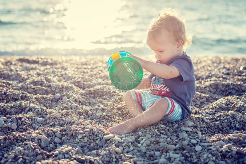 Garçon mignon d'enfant en bas âge jouant sur la plage images stock