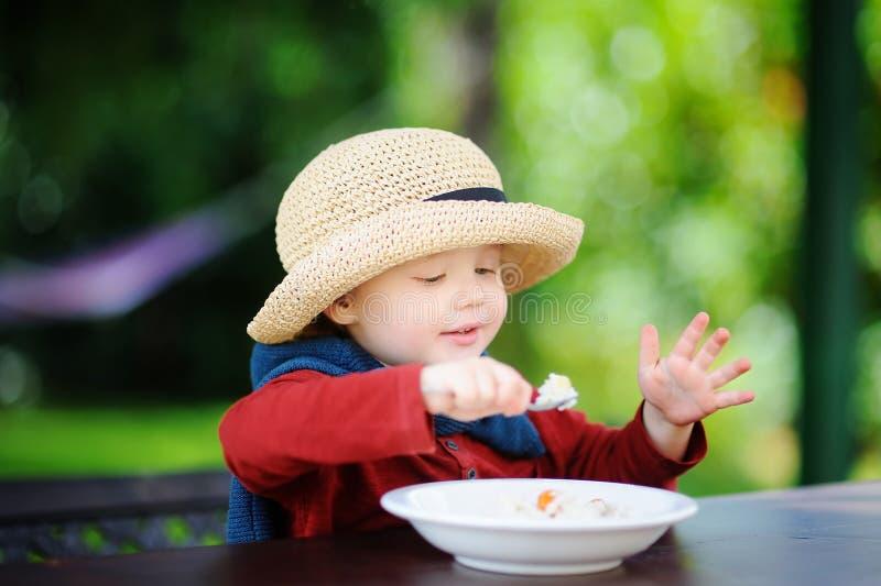 Garçon mignon d'enfant en bas âge mangeant de la céréale de riz dehors photographie stock libre de droits