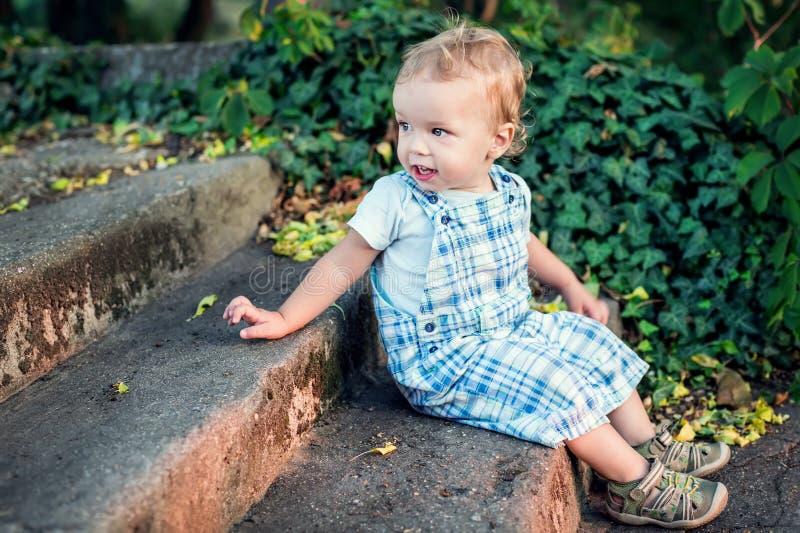 Garçon mignon d'enfant en bas âge s'asseyant sur les escaliers photo libre de droits