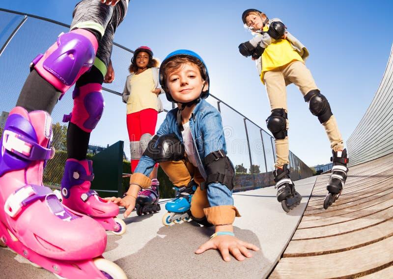 Garçon mignon dans des patins de rouleau ayant l'amusement avec des amis image stock