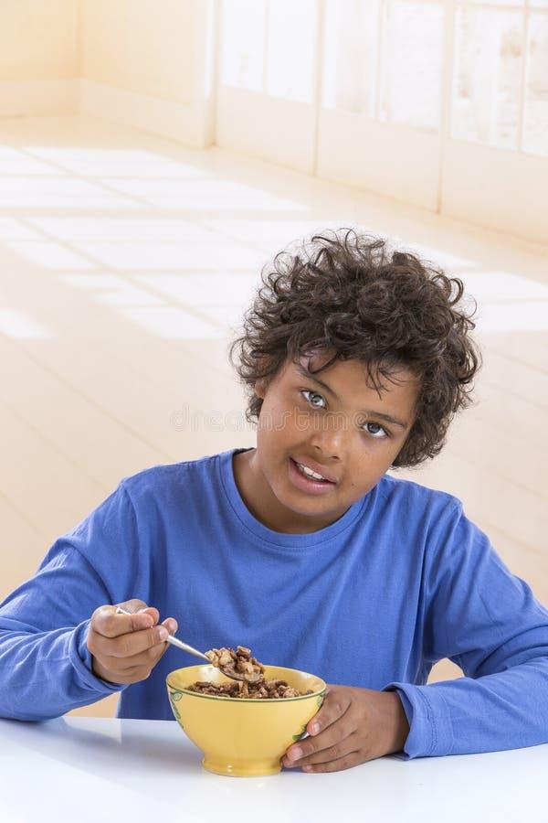 Garçon mignon dans le T-shirt bleu mangeant des céréales pour le petit déjeuner à l'arrière-plan de cuisine photo libre de droits