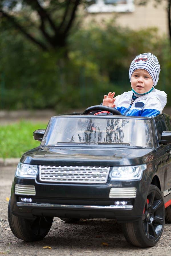 Garçon mignon en montant une voiture électrique noire en parc photographie stock