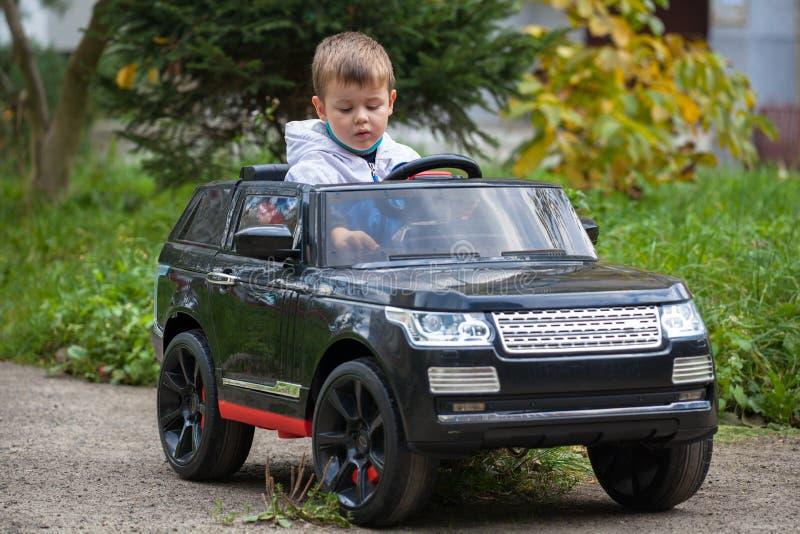 Garçon mignon en montant une voiture électrique noire en parc photos stock