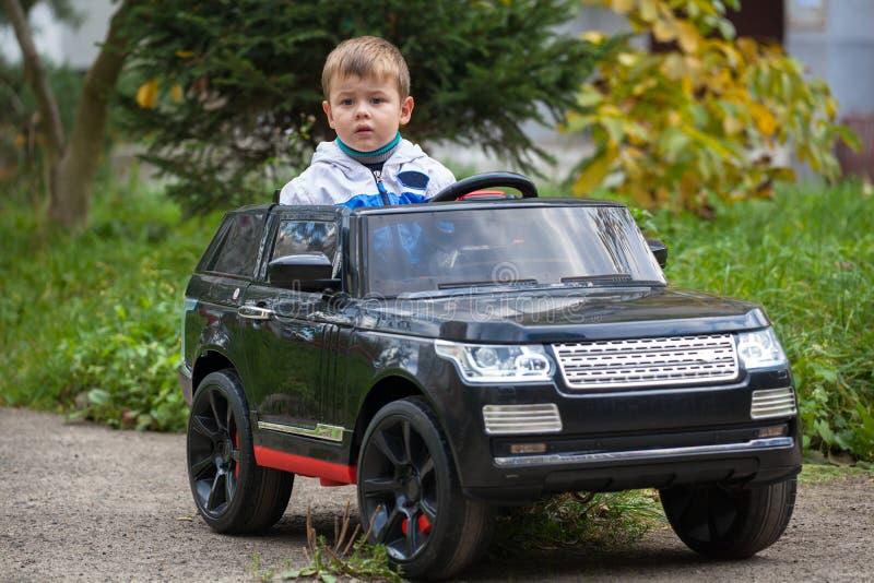 Garçon mignon en montant une voiture électrique noire en parc image stock