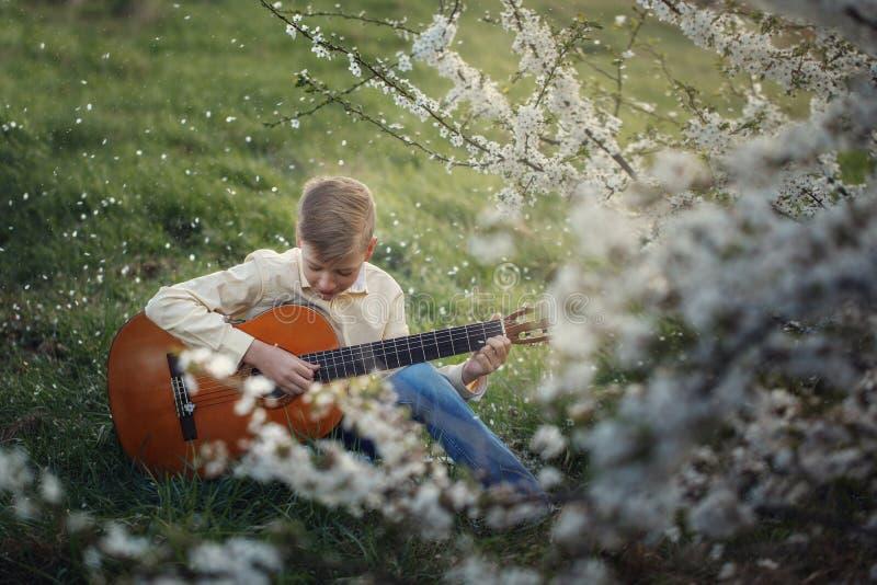 Garçon mignon faisant la musique jouant la guitare sur la nature images stock