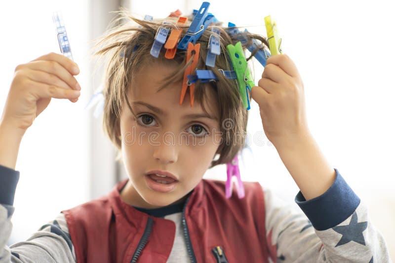 Garçon mignon jouant avec des crochets de blanchisserie photos stock
