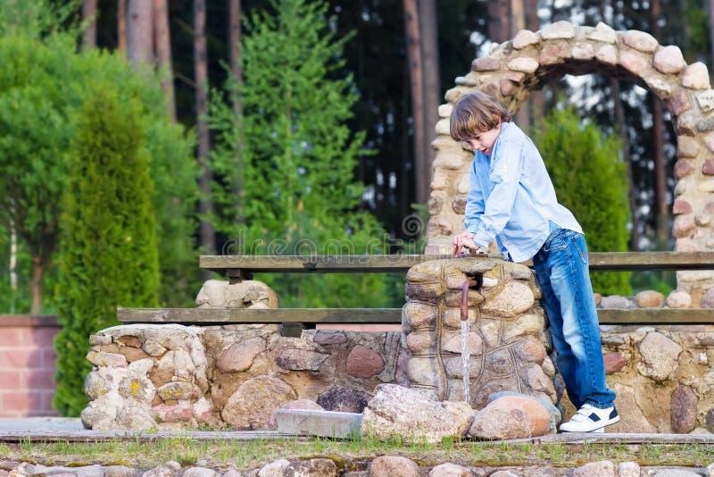 Garçon mignon jouant avec une pompe à eau photos libres de droits
