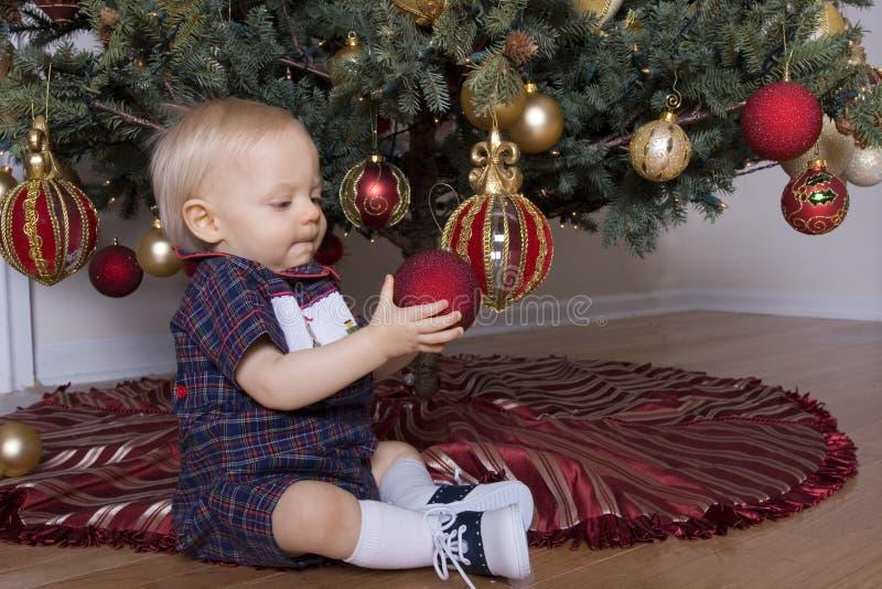 Garçon mignon jouant sous l'arbre de Noël image stock