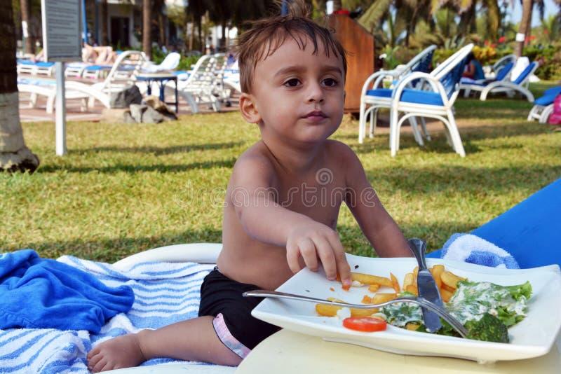 Garçon mignon mangeant au parc photos libres de droits