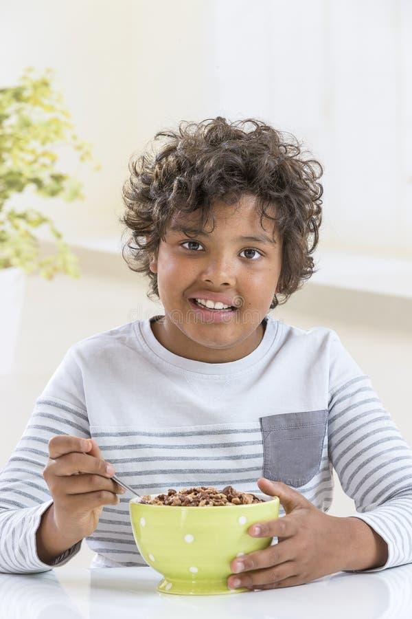 Garçon mignon mangeant des céréales pour le petit déjeuner à l'arrière-plan de cuisine images libres de droits