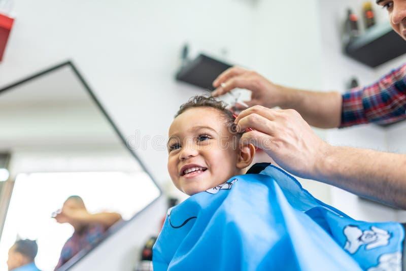 Garçon mignon obtenant une coupe de cheveux dans Barber Shop Concept de beauté photos stock