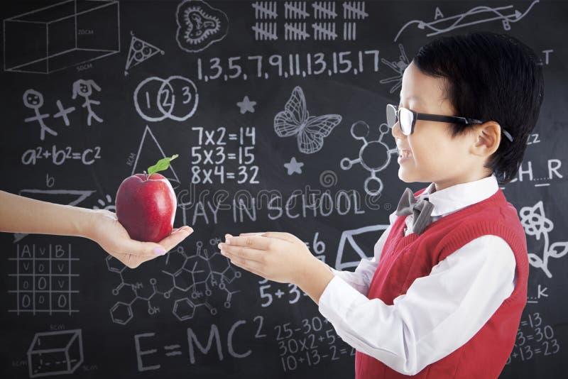 Garçon mignon recevant la pomme fraîche photo libre de droits
