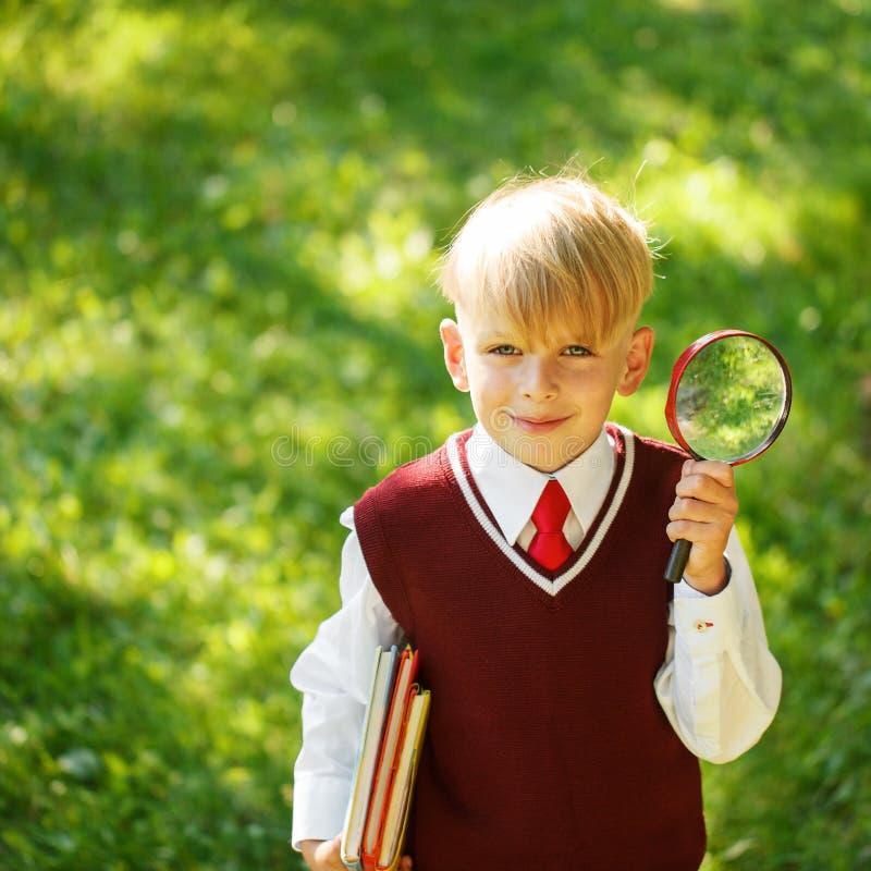 Garçon mignon retournant à l'école Enfant avec les livres et la loupe sur le sapin photographie stock libre de droits