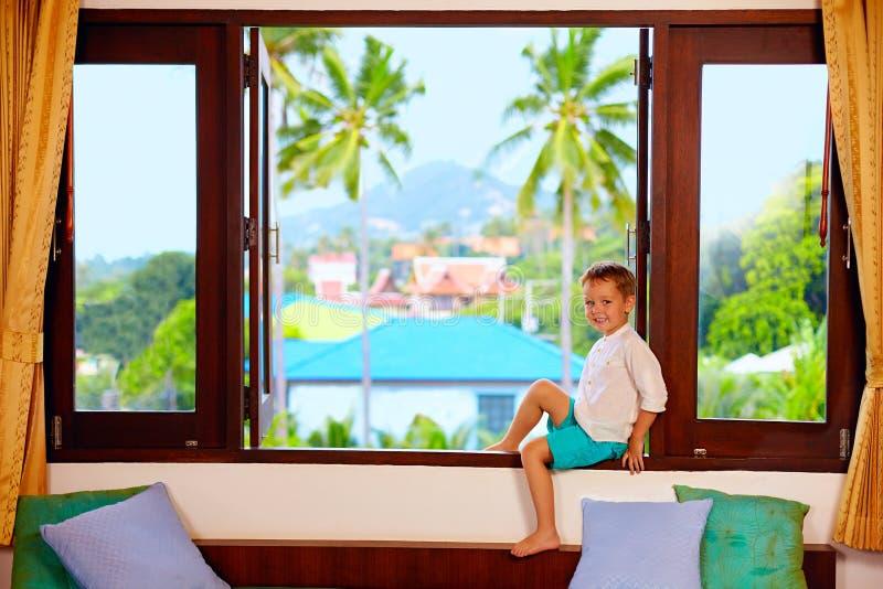 Garçon mignon s'asseyant sur le filon-couche de fenêtre dans les tropiques photographie stock libre de droits