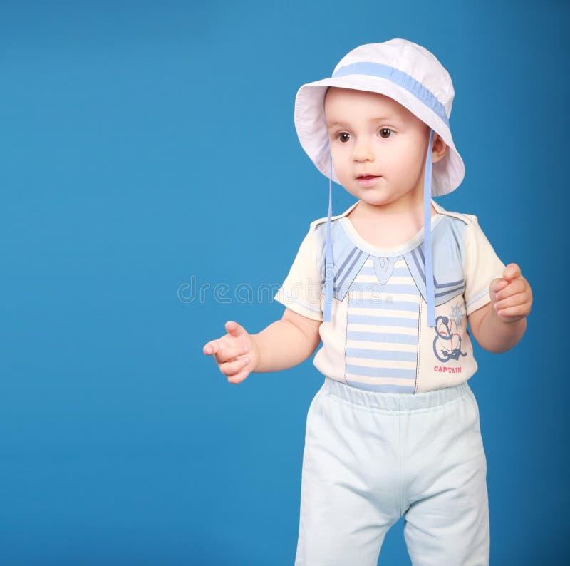 Garçon mignon se tenant sur un fond bleu portant un marin photo stock