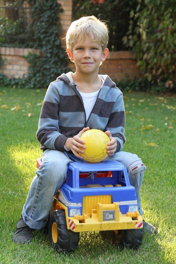Garçon mignon sur un camion de jouet photographie stock